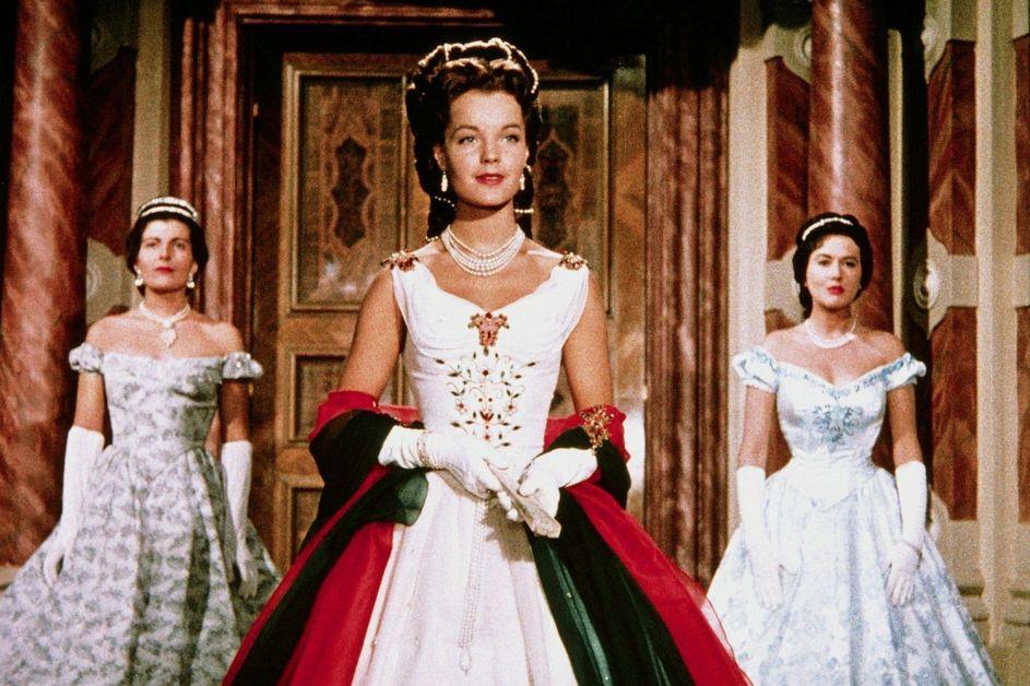 Sissi steht vor ihrem Thron. Neben ihr zwei ihrer Hofdamen